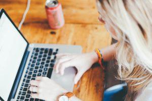 Kobieta wypełniająca wniosek przy komputerze - pożyczka